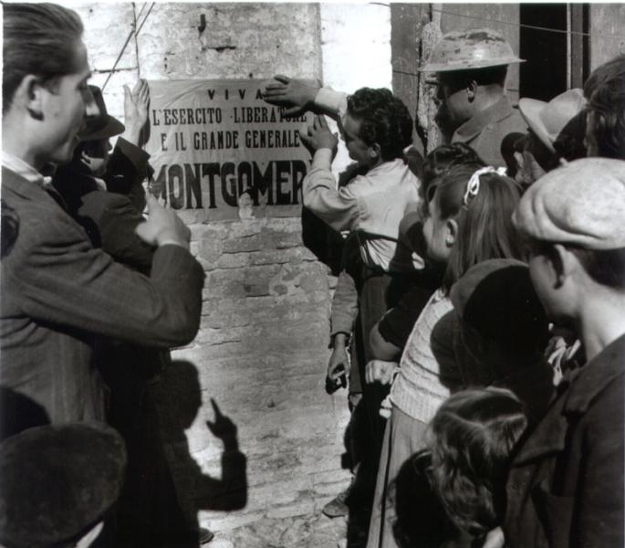 """6 novembre 1943. Vasto. """"I cittadini si preparano all'entrata dell'8ª Armata. Alcuni di essi stanno attaccando un manifesto di benvenuto agli uomini di Montgomery"""" (da G. Artese, La guerra in Abruzzo e Molise 1943-44, vol. I, per gentile concessione dell'Imperial War Museum - London)."""